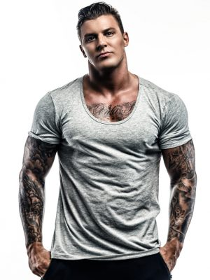 Handsome strong tattooed man in grey t shirt isolated on white background.